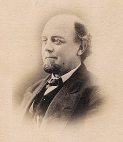 A sepia-toned portrait of the head and shoulders of a balding man with dark hair, a trim beard, and no mustache.