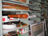 Metal shelving with various items on each shelf like signs, beer cans, wooden containers, and boxes.