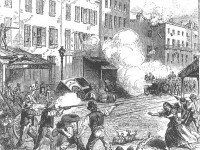 An engraving showing men firing down a city street at soldiers with cannons. Several dead and wounded are on the ground and a woman rushes toward one of them.