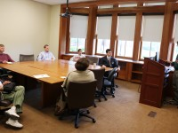 A group of people sitting around a conference table in a classroom listening to a man standing at a lecturn.