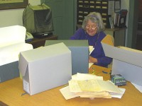 Older woman sitting at a table with archival boxes and piles of paper on it.
