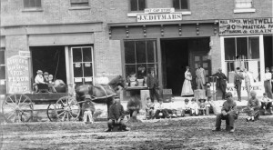 People sitting along muddy street curb outside Herrick's Head Center for Flour and Feed, J.V. Ditmars Hat and Cap store, and Whitwell Wallpaper.