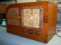 Old-fashioned wooden radio with three dials and a built-in speaker.