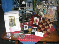 Table with wine glasses, matted prints, magnets, wine stoppers and other wine-related items for sale.
