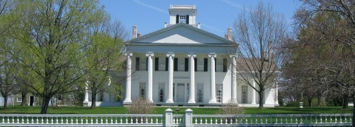 An early spring view of a white 6-columned mansion from the road showing a fence and gate by the road.