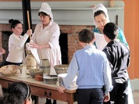 Women in old-fashioned dress churning butter and mixing batter with chldren.