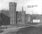 Black and white photo of a castle-like building on Main Street in Geneva. A cannon sits on the lawn next to a large white sign with a V at the top center over a Kiwanis logo.