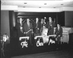 Six men standing with their instruments (trumpet, drumsticks, 2 saxaphones, an upright bass and a piano) behind stands that read The Chess Men.