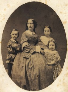 Seated woman in a full skirt surrounded by 3 children.