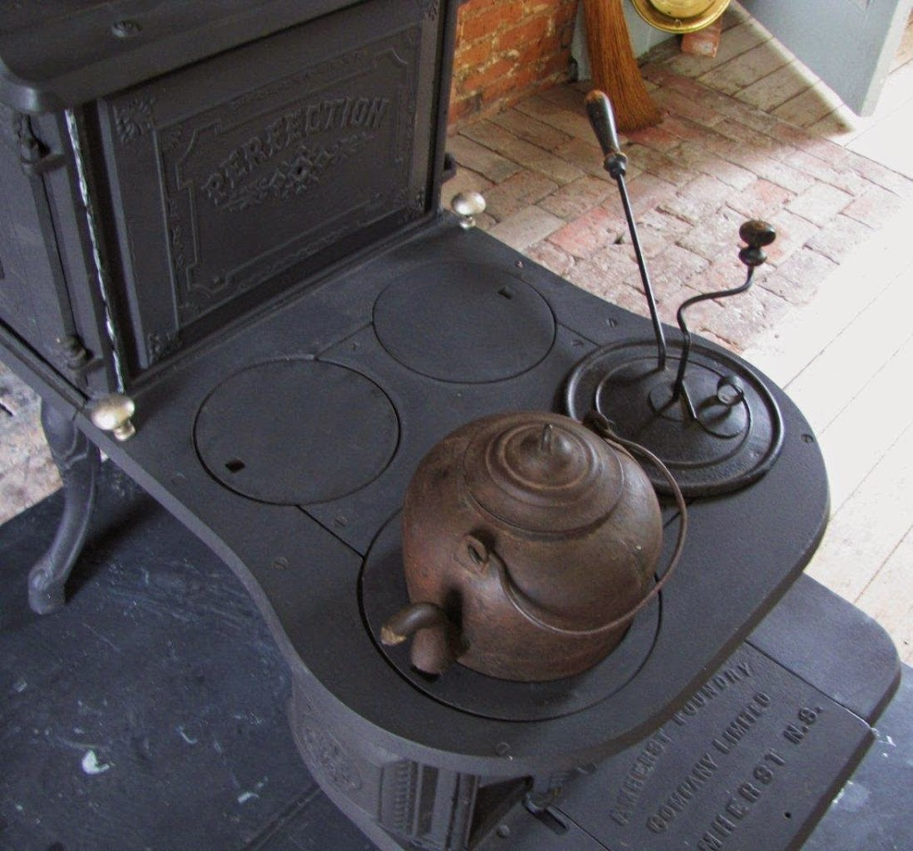 A cast iron tea kettle and coffee roaster on sit an 1850 step stove.