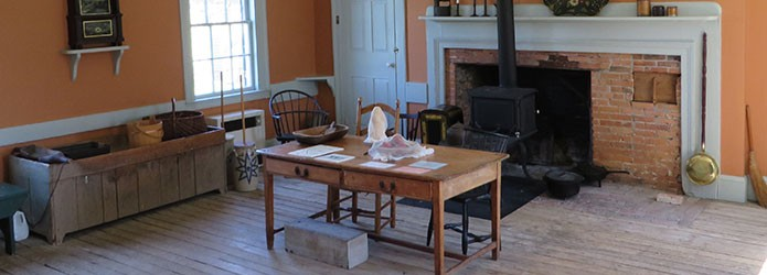 A room with a cast iron stove in front of a fireplace with a bake oven. Furnished with a table, dry sink, chairs, a clock, and butter churns.