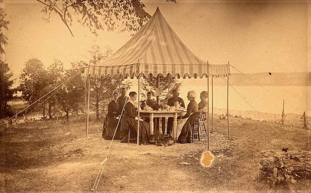Seven people in old-fashioned dress sitting around a table set for tea under a tent looking out on a lake.