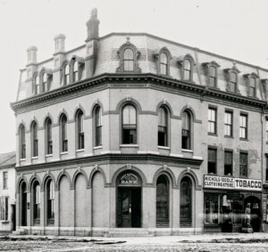 Black and white picture of a building with a mansard roof and door labeled First National Bank.