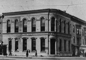 Black and white picture of a building on a corner with a cornice labeled The Geneva National Bank.
