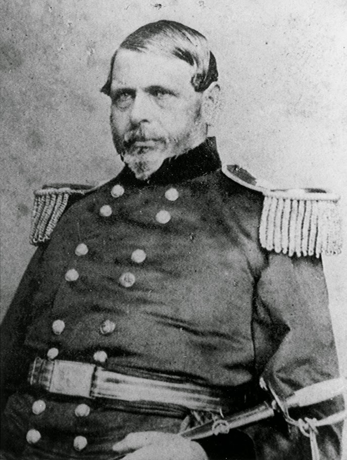 Bearded man in a military uniform sitting with a sword across his lap.