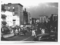 view-of-seneca-street-with-sailors-crossing-the-street-in-the-1940s