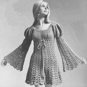 Black and white image of women wearing a crocheted dress with Juliet sleeves.