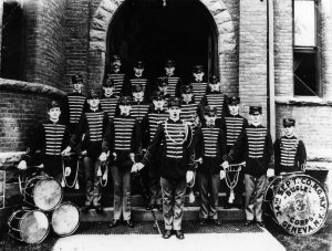 Black and white photo of a military band outside of the Armory in Geneva.