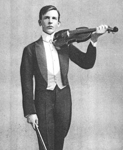 Black and white photo of a man in a tuxedo posing with a violin