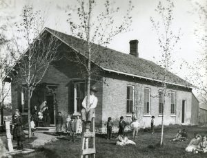 A one-room brick schoolhouse with two teachers and a group of children sitting and standing in the yard.