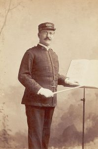 man in uniform standing in front of a music stand