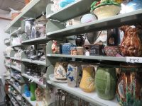 view-of-shelves-filled-with-pitchers-and-china-in-storage