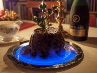 A brown, rounded pudding on a silver tray with a holly sprig inserted in the top and blue flames around the circumference.