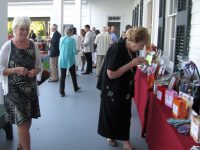 People looking at raffle items on the veranda at Rose Hill Mansion during a fundraiser.