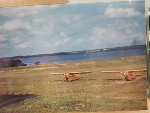 Two grounded airplanes near a lake