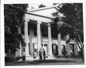 two men standing in front of a house