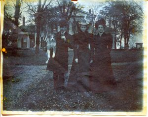 A man holding a dog and two women standing in front of a house.