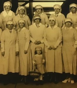 women and a little girl in American Red Cross uniforms