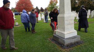 People in rain gear gathered near an obelisk in a cemetery.