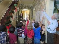 Woman with children in a hallway pointing up to Christmas greenery on the bannister.