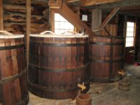 Three large wooden beer barrels with taps.