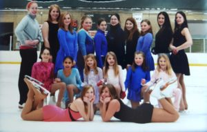 young ladies wearing ice skating outfits posed in an ice skating rink