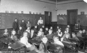 26 students standing by a blackboard or sitting in old-fashioned desks in rows with a teacher looking on.