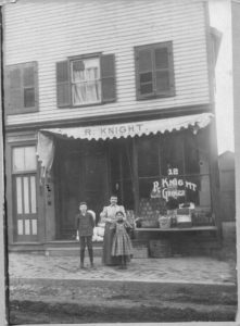 a woman and two children standing in front of a multi-story building