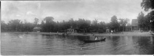 man in a canoe with people, canoes and four houses along the shore line