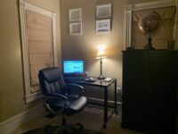 In between a window and a cupboard is an office chair and a table with a lamp and computer on it.