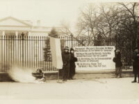 women with banners and a fire in a urn stand outside the White House