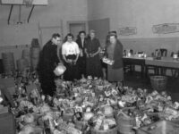 A man and four women surrounded by baskets of food collected and organized by the Salvation Army