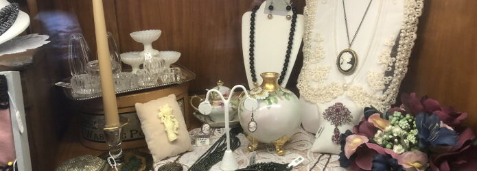 Shelf display of a silver box, candlestick, glass knick-knacks, beaded necklaces, cameo jewelry and silk flowers.