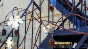 Copper sculpture of a grapevine twisting around fire escape steps.