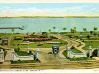 Postcard image of a car driving into a manicured lakeside park