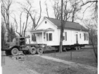 single story house being towed by a truck