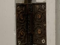 Close-up of a iron door hinge in the Housman home