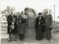 three men and a woman standing around a boulder