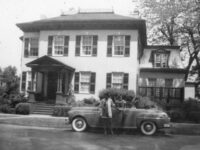two people and car in front of a multi-story house