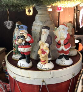 Santa figurines with dates on base arranged on a toy drum under a Christmas tree.